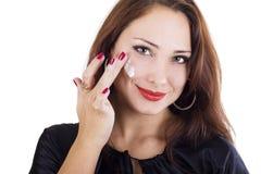 Frau, die Sahne auf ihrem Gesicht aufträgt Lizenzfreies Stockbild