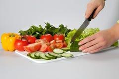 Frau, die Salat schneidet Stockfotografie