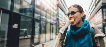 Frau, die Sandwich und das Gehen isst Stockfotos