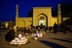 Frau, die Schädelschutzkappen vor Moschee verkauft Lizenzfreie Stockfotos