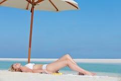 Frau, die am schönen Strand-Feiertag ein Sonnenbad nimmt Stockbilder