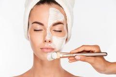 Frau, die Schönheitshaut-Maskenbehandlung auf Gesicht mit Bürste erhält Stockbild