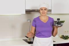 Frau, die Schöpflöffel und Topf in der Küche hält lizenzfreies stockfoto