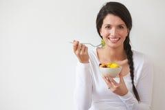 Frau, die Schüssel frische Frucht gegen weißen Hintergrund isst Stockfotos