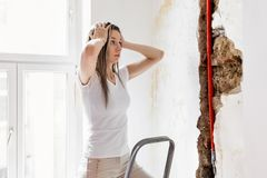 Frau, die Schaden nach einem Wasserleitungsleck betrachtet lizenzfreie stockfotos