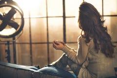 Frau, die Schale des Getränkes in der Dachbodenwohnung genießt lizenzfreies stockfoto