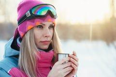 Frau, die Schale von der Thermosflasche in den Händen an den schneebedeckten Niederlassungen des Winterbaumhintergrundes hält Lizenzfreies Stockfoto