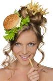 Frau, die Scheibe der Kartoffel am Mund hält Stockfoto