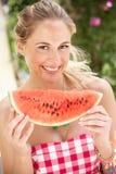 Frau, die Scheibe der Wassermelone genießt Lizenzfreie Stockfotos