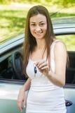 Frau, die Schlüssel des Neuwagens zeigt stockfoto