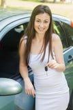 Frau, die Schlüssel des Neuwagens zeigt stockbild