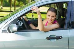 Frau, die Schlüssel des Neuwagens zeigt lizenzfreies stockfoto