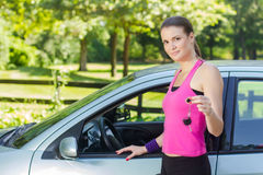 Frau, die Schlüssel des Neuwagens zeigt lizenzfreie stockfotos