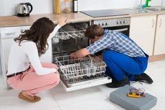 Frau, die Schlosser Repairing Dishwasher betrachtet Stockfotografie