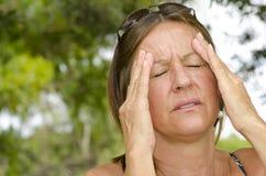 Frau, die schmerzliche Kopfschmerzen erleidet Lizenzfreies Stockbild