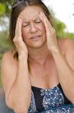 Frau, die schmerzliche Kopfschmerzen erleidet Stockfotos