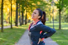 Frau, die schmerzliche Rückseite im Park hält Stockfotos
