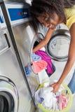 Frau, die schmutzige Kleidung in der Waschmaschine lädt Lizenzfreie Stockfotos
