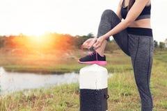 Frau, die Schnürsenkel bindet Weiblicher Sporteignungsläufer, der gelesen erhält stockbilder