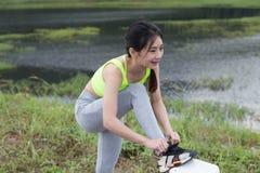 Frau, die Schnürsenkel bindet Weiblicher Sporteignungsläufer, der gelesen erhält stockfoto