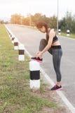 Frau, die Schnürsenkel bindet Weiblicher Sporteignungsläufer, der gelesen erhält stockfotos