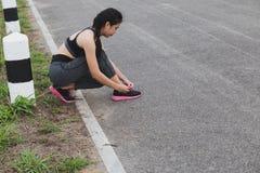 Frau, die Schnürsenkel bindet Weiblicher Sporteignungsläufer, der gelesen erhält lizenzfreies stockbild