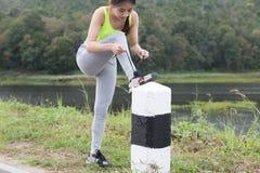 Frau, die Schnürsenkel bindet Weiblicher Sporteignungsläufer, der gelesen erhält stockbild