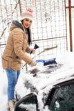 Frau, die Schnee auf Auto entfernt Lizenzfreie Stockfotografie