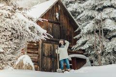 Frau, die Schnee in der Landschaft schaufelt Lizenzfreie Stockbilder