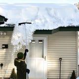 Frau, die Schnee des Dachs mit Schneerührstange hinabzieht Stockfoto