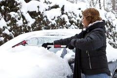 Frau, die Schnee von ihrem Auto löscht Stockfotos