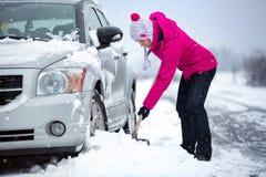 Frau, die Schnee von ihrem Auto schaufelt Lizenzfreie Stockbilder