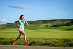 Frau, die schnell auf Landschaftsstraße läuft Stockfoto