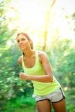 Frau, die schnell in Wald läuft Stockfotografie