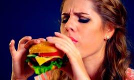 Frau, die Schnellimbiß isst Mädchen, das köstlichen Hamburger genießt Lizenzfreie Stockfotografie