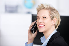 Frau, die schnurloses Telefon beim oben schauen im Büro verwendet Stockbild