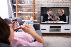 Frau, die Schokolade beim Fernsehen isst stockbild