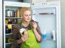 Frau, die Schokolade vom Kühlschrank isst Stockbilder
