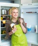Frau, die Schokolade vom Kühlschrank isst Lizenzfreie Stockfotos