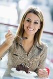 Frau, die Schokoladenkuchen im Kaffee isst Lizenzfreies Stockfoto