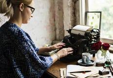 Frau, die schreibenden Retro- Schreibmaschinen-Maschinen-Arbeits-Verfasser verwendet Lizenzfreies Stockbild