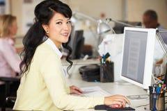 Frau, die am Schreibtisch im besetzten kreativen Büro arbeitet stockbilder
