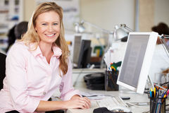 Frau, die am Schreibtisch im besetzten kreativen Büro arbeitet