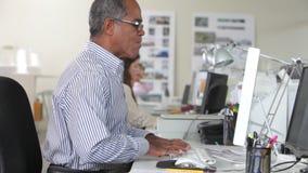 Frau, die am Schreibtisch im besetzten kreativen Büro arbeitet stock video footage