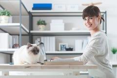 Frau, die am Schreibtisch mit ihrer Katze arbeitet Lizenzfreie Stockbilder