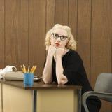 Frau, die am Schreibtisch sitzt lizenzfreie stockfotos