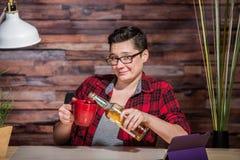 Frau, die am Schreibtisch trinkt Stockfoto