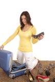 Frau, die Schuh in Koffer einsetzt stockbild