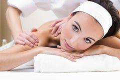 Frau, die Schultermassage am Schönheitsbadekurort genießt Stockfotografie