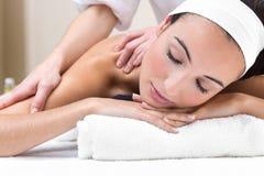 Frau, die Schultermassage am Schönheitsbadekurort genießt Stockfoto